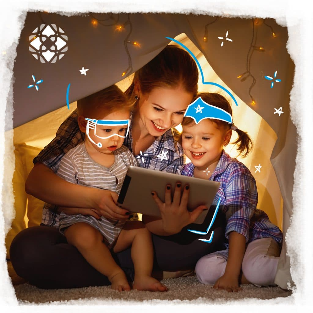 Foto de uma mãe, sorrindo, com seus dois filhos numa cabana de cobertores utilizando um app infantil no iPad. Uma criança de aproximadamente dois anos e outra criança, sorrindo, de aproximadamente quatro anos. Há ilustrações de estrelas, um óculos com microfone na criança mais nova e uma tiara do poder.