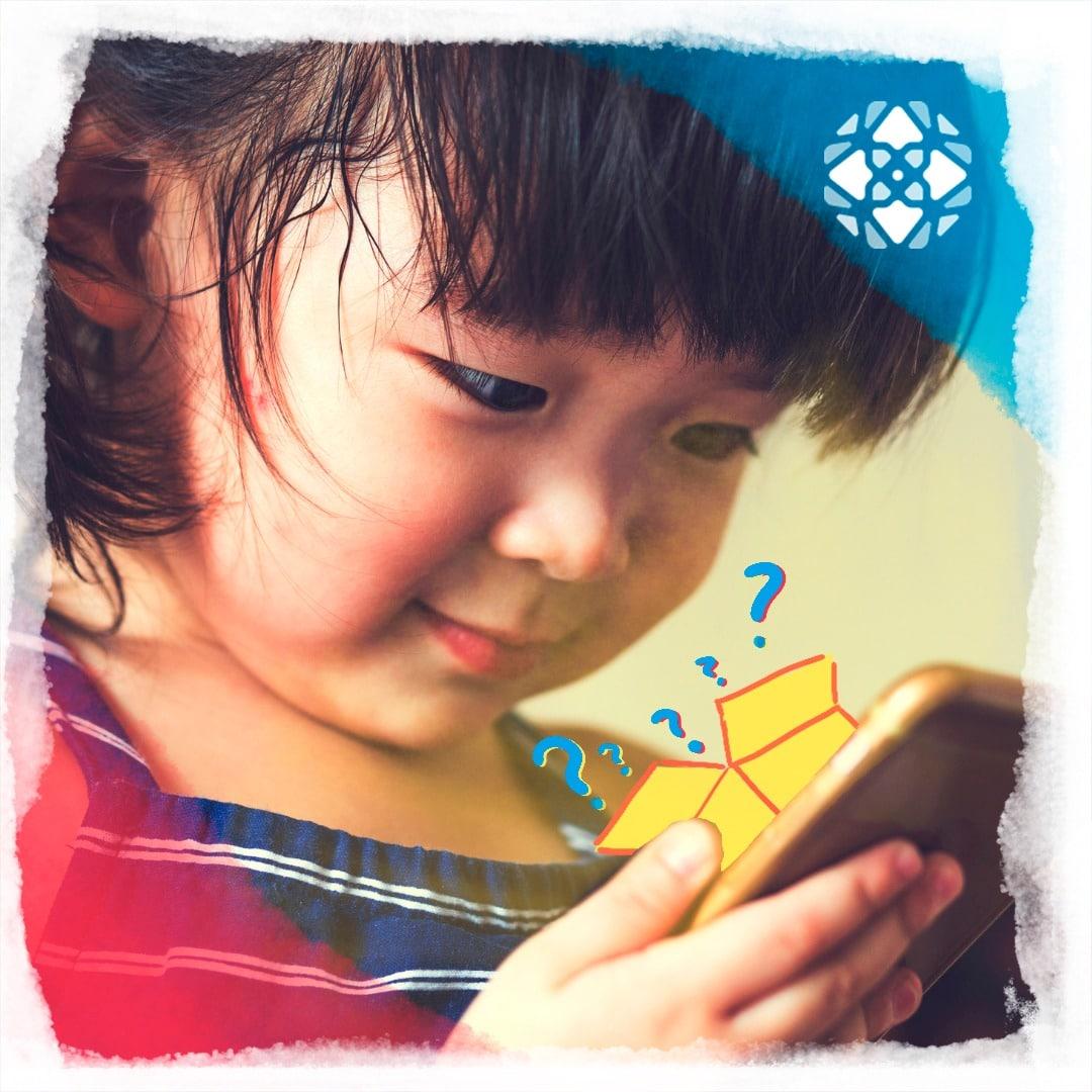 Criança (menina) de cerca de quatro anos mexendo num celular. Ilustração de uma caixa amarela com pontos de interrogação saindo representam uma loot box